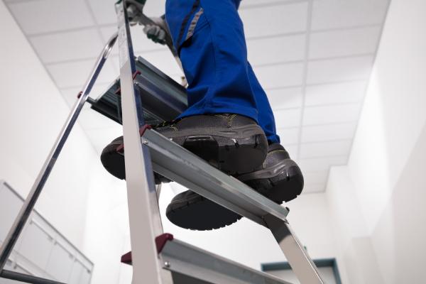 A person climbing a ladder in an office