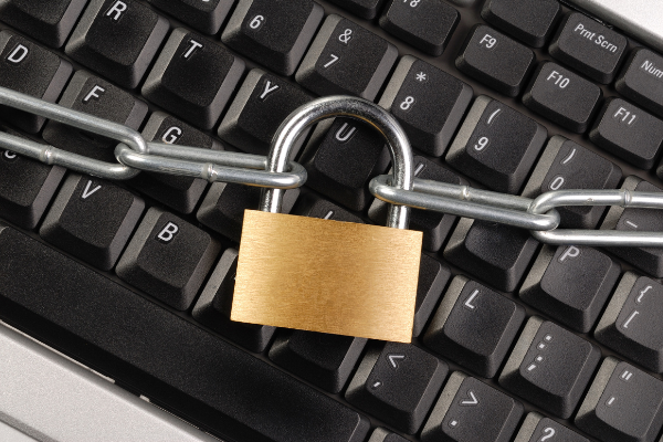 A security padlock and chains resting on a computer keyboard